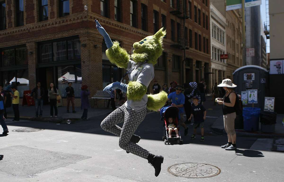 A woman in a furry costume attempts to pop a bubble during the annual How Weird Street Festival on Howard Street in San Francisco, Calif. Sunday, April 26, 2015.