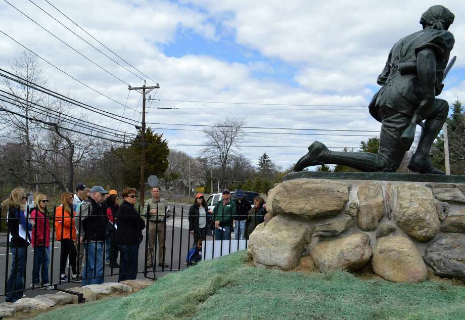 A walking tour group pauses at the Minute Man Monument on Sunday to learn about the local militia -- paid tribute by the 105-year-old statue -- who fought British invaders during the Battle of Compo in April 1777. Photo: Jarret Liotta / Westport News