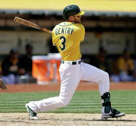 Oakland Athletics' Craig Gentry swings for an RBI-single in the fourth inning of a baseball game against the Houston Astros, Sunday, April 26, 2015, in Oakland, Calif. (AP Photo/Ben Margot)