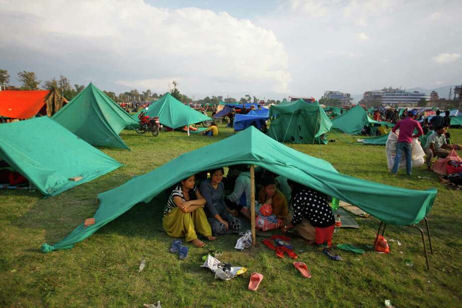 Nepalese, fearing aftershocks, take shelter Sunday in makeshift tents in an open ground in Kathmandu. Photo: Niranjan Shrestha, STF / AP