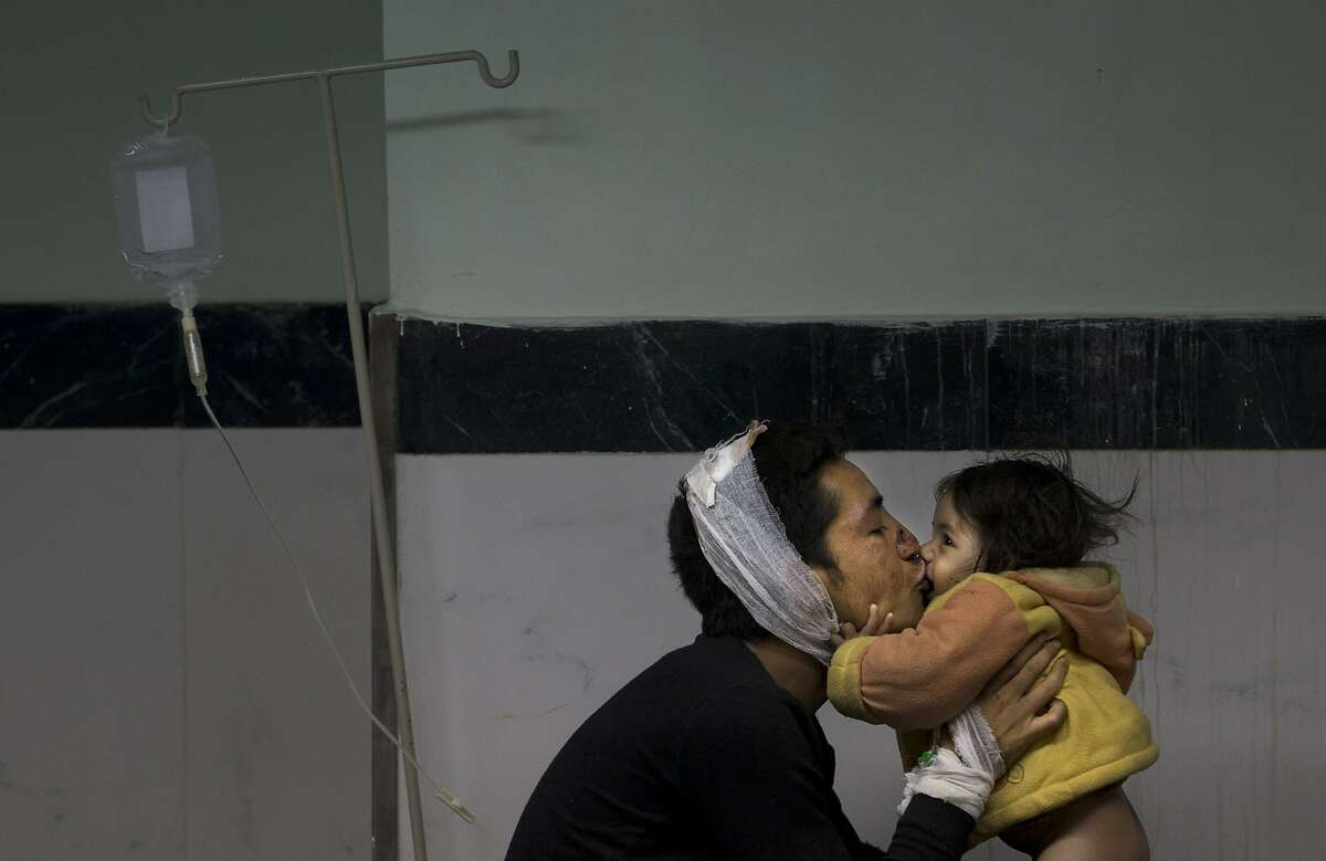 Earthquake injured Nepalese man Suresh Parihar plays with his daughter Sandhya at a hospital, in Kathmandu, Nepal, Sunday, April 26, 2015. A strong magnitude 7.8 earthquake shook Nepal's capital and the densely populated Kathmandu Valley before noon Saturday, causing extensive damage with toppled walls and collapsed buildings, officials said.