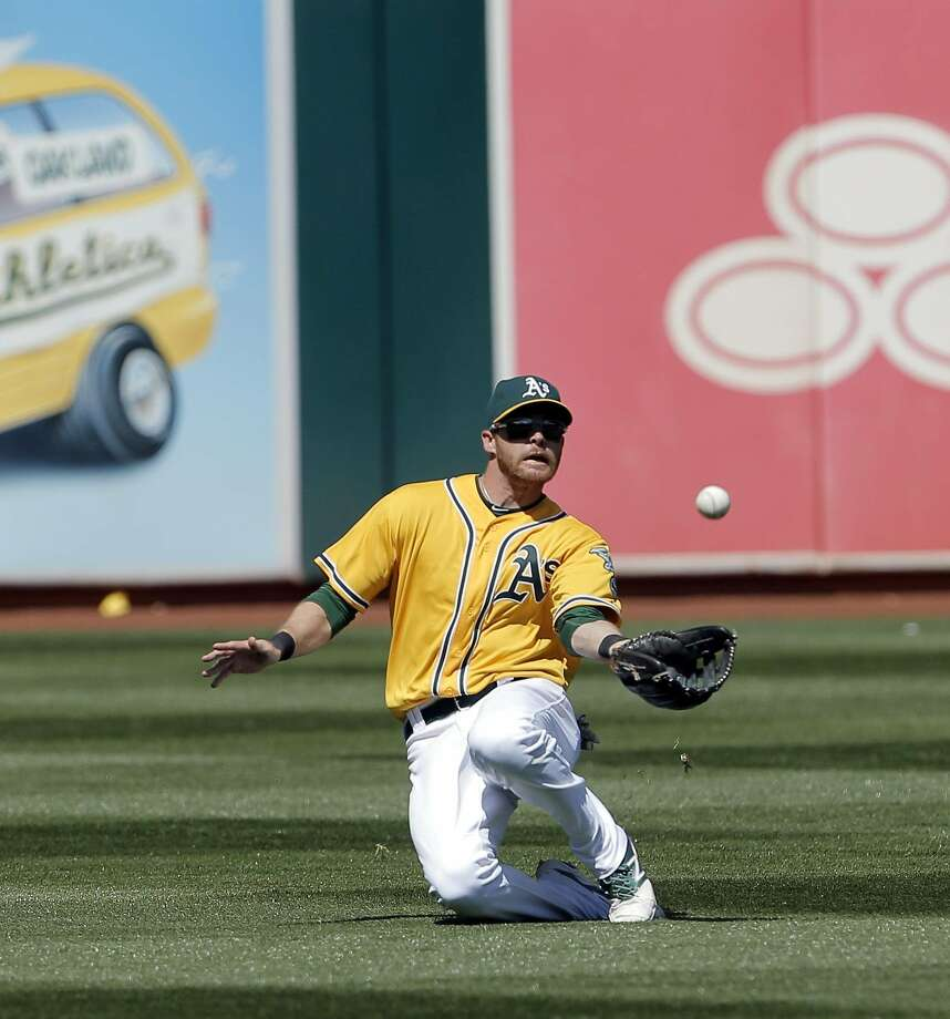 Craig Gentry (3) catches a ball hit by Evan Gattis (11) in the fifth inning. The Oakland Athletics played the Houston Astros at O.co Coliseum in Oakland, Calif., on Sunday, April 26, 2015. The Astros won 7-6. Photo: Carlos Avila Gonzalez, The Chronicle