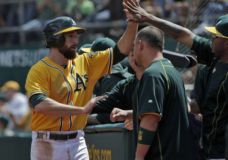 Ike Davis (17) is high fived after scoring in the fourth on a single hit by Brett Lawrie. The Oakland Athletics played the Houston Astros at O.co Coliseum in Oakland, Calif., on Sunday, April 26, 2015. The Astros won 7-6. Photo: Carlos Avila Gonzalez, The Chronicle