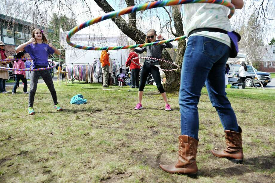 Best friends, Alana Weber, left, 12,  and Carly Dell, right, 11, both from Niskayuna, try out hula hoops as they watch Jennifer Mapes, owner of Hoops by Jem, demonstrate the technique at the The 23rd annual Cherry Blossom Festival, put on by the Congregation Gates of Heaven on Sunday, April 26, 2015, in Schenectady, N.Y.  The money raised through the 5K race and the 2K walk benefit the St. Peters Regional ALS Center.    (Paul Buckowski / Times Union) Photo: PAUL BUCKOWSKI / 00031352A