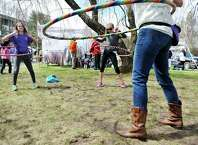 Best friends, Alana Weber, left, 12,  and Carly Dell, right, 11, both from Niskayuna, try out hula hoops as they watch Jennifer Mapes, owner of Hoops by Jem, demonstrate the technique at the The 23rd annual Cherry Blossom Festival, put on by the Congregation Gates of Heaven on Sunday, April 26, 2015, in Schenectady, N.Y.  The money raised through the 5K race and the 2K walk benefit the St. Peters Regional ALS Center.    (Paul Buckowski / Times Union)