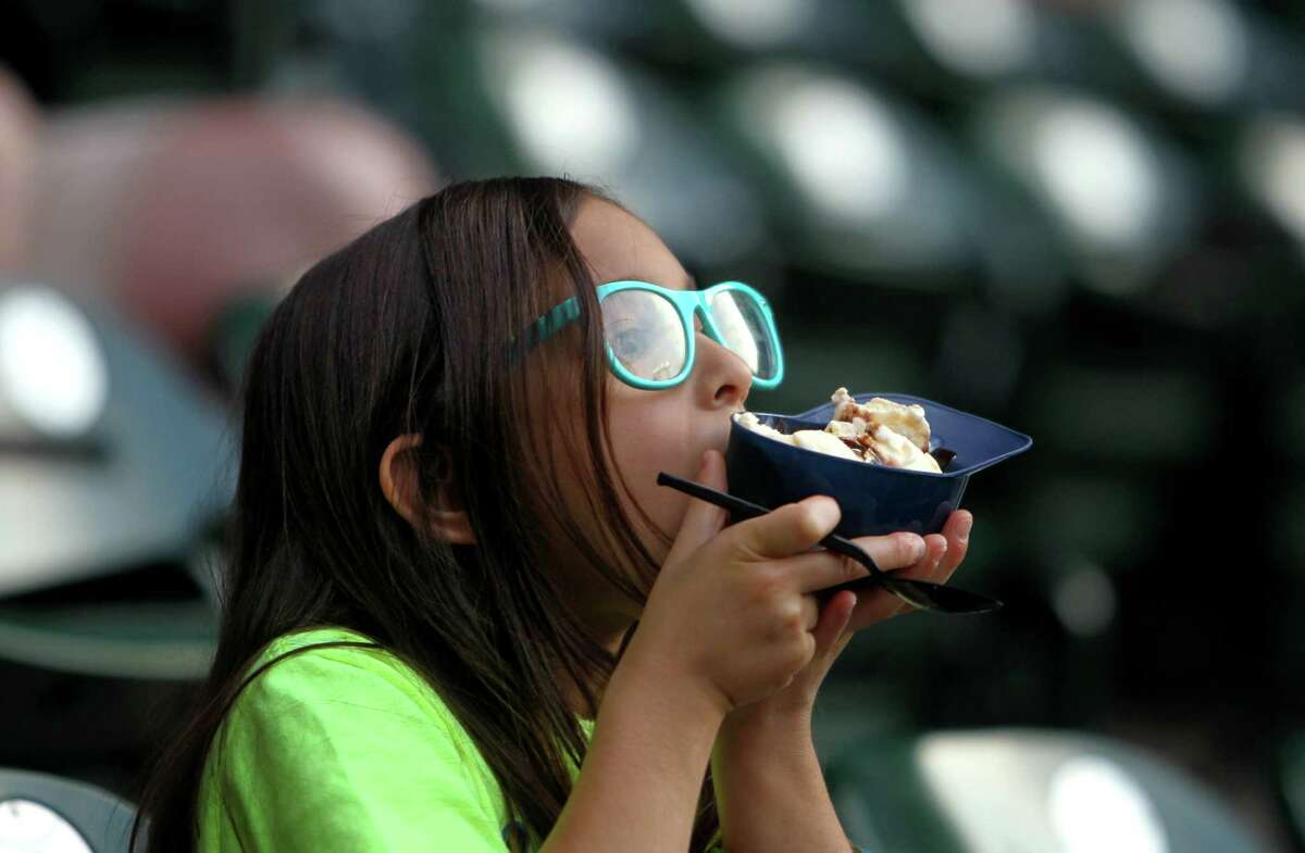 Emma Garcia, eight, of Alvin, eats Blue Bell ice cream at Minute Maid Park Wednesday, April 15, 2015, in Houston, Texas. ( Gary Coronado / Houston Chronicle )