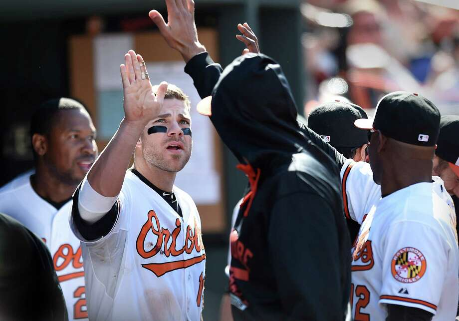 Baltimore Orioles' Chris Davis is congratulated by a team mate in the dugout after scoring against the Boston Red Sox in the seventh inning of a baseball game, Sunday, April 26, 2015, in Baltimore. The Orioles won 18-7. (AP Photo/Gail Burton) ORG XMIT: MDGB114 Photo: GAIL BURTON / FR4095 AP