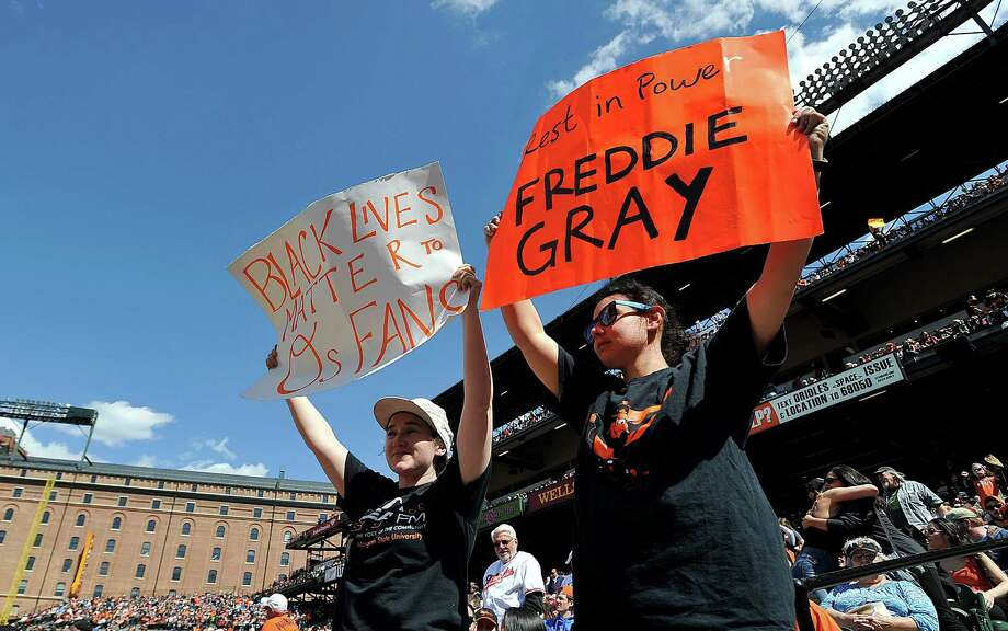 Baseball fans hold Freddie Gray demonstration signs at the Baltimore Orioles and Boston Red Sox game Sunday in Orioles Park at Camden Yards. Photo: GAIL BURTON, FRE / FR4095 AP