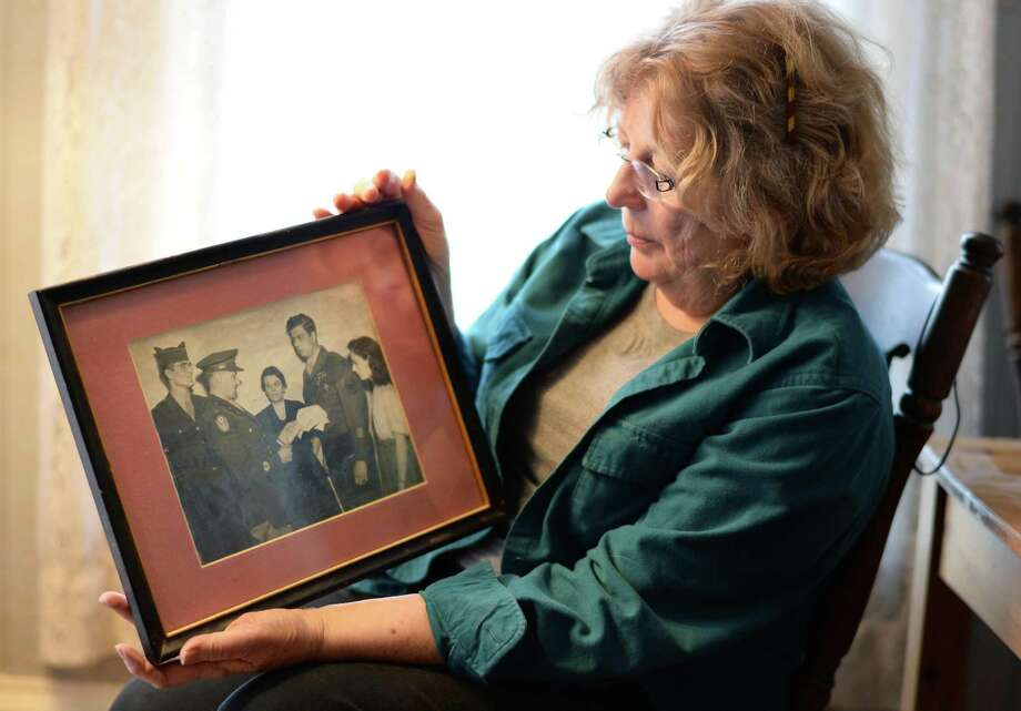 Sandra Marnell holds a photograph of her father, then T. Sgt. Richard Marnell receiving the Distinguished Service Cross in 1946, at her home Friday April 17, 2015 in Duanesburg, NY. A member of an elite Ranger unit, Marnell served 27 months in combat and was wounded three times during WWII.   (John Carl D'Annibale / Times Union) Photo: John Carl D'Annibale / 00031482A