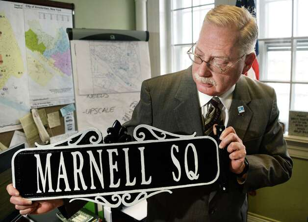 City historian Robert von Hasseln with the new Marnell Square sign to recognize the late Richard Marnell, a decorated WWII veteran from Amsterdam, at his office in City Hall Thursday April 23, 2015 in Amsterdam, NY.  (John Carl D'Annibale / Times Union) Photo: John Carl D'Annibale / 00031577A