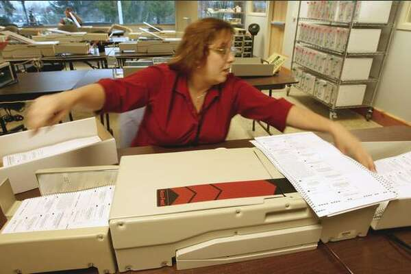 King County elections worker Nance Knutson counts ballots Thursday at the Tukwila site with some of the older machines.