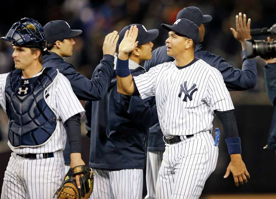 New York Yankees designated hitter Alex Rodriguez celebrates with teammates after the Yankees defeated the New York Mets 6-4 in a baseball game at Yankee Stadium in New York, Sunday, April 26, 2015.  New York Yankees catcher John Ryan Murphy is at left. (AP Photo/Kathy Willens) ORG XMIT: NYY119 Photo: Kathy Willens / AP