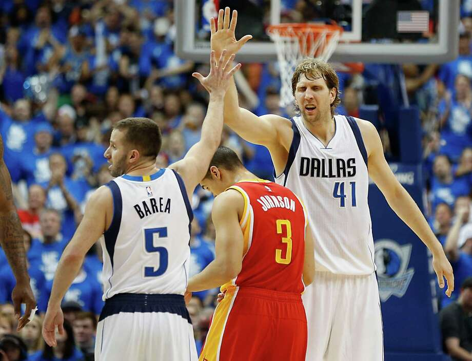 Guard J.J. Barea  left, who started for the Mavericks and provided a spark with 17 points and 13 assists, celebrates with Dirk Nowitzki as Rockets guard Nick Johnson crashes the party. Nowitzki added 16 points and eight rebounds to help Dallas extend its season. Photo: James Nielsen, Staff / © 2015  Houston Chronicle