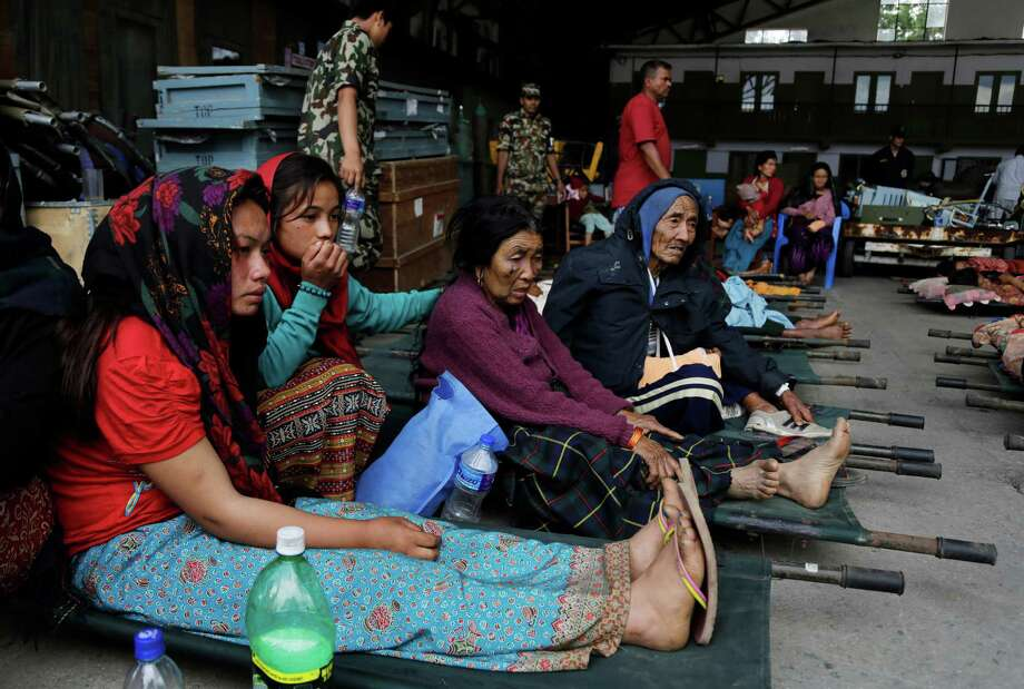 Victims of Saturday's earthquake sit on stretchers as they wait for ambulances after being evacuated Monday at the airport in Kathmandu, Nepal. Photo: Altaf Qadri, AP / AP