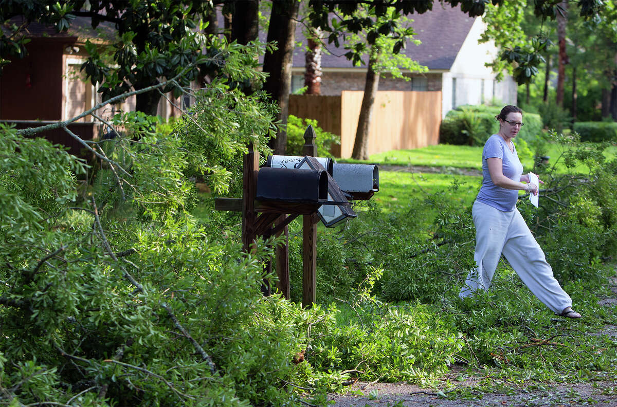 Elaine Spratt steps through downed trees after checking her mail after a storm swept through Panorama Village, Monday, April 27, 2015, in Conroe, Texas.