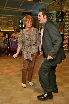 Aug. 26, 2006: From left to right, patron Carol Duncan dances along with cast member Heath Harper during The Soapranos dinner show. Photo: Bill Olive, FOR THE CHRONICLE / FREELANCE