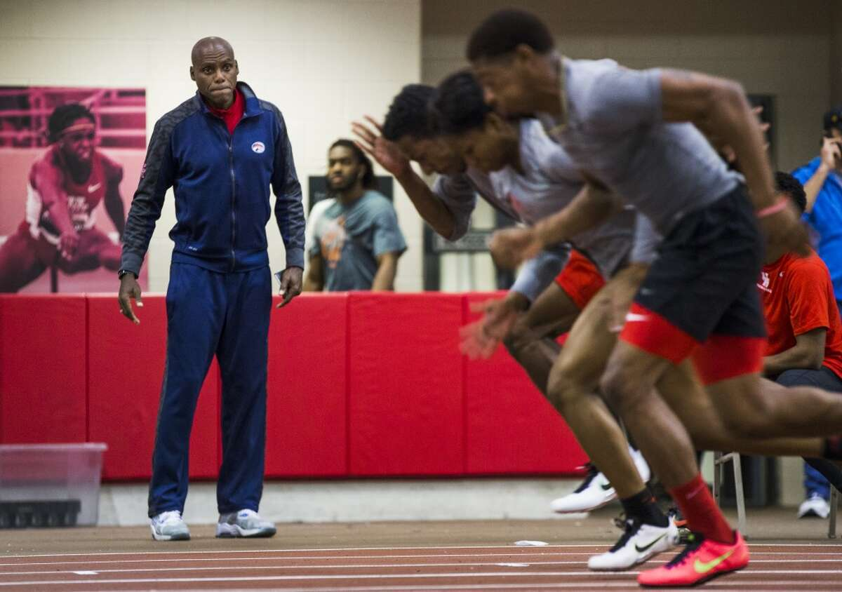 Carl Lewis watches a group of sprinters as they work on their starts at the University of Houston indoor track on Wednesday, Feb. 18, 2015, in Houston. The former UH track star and nine time Olympic gold medalist has joined the Cougars' track and field program as an assistant coach, and will help with sprints and jumps.( Brett Coomer / Houston Chronicle )