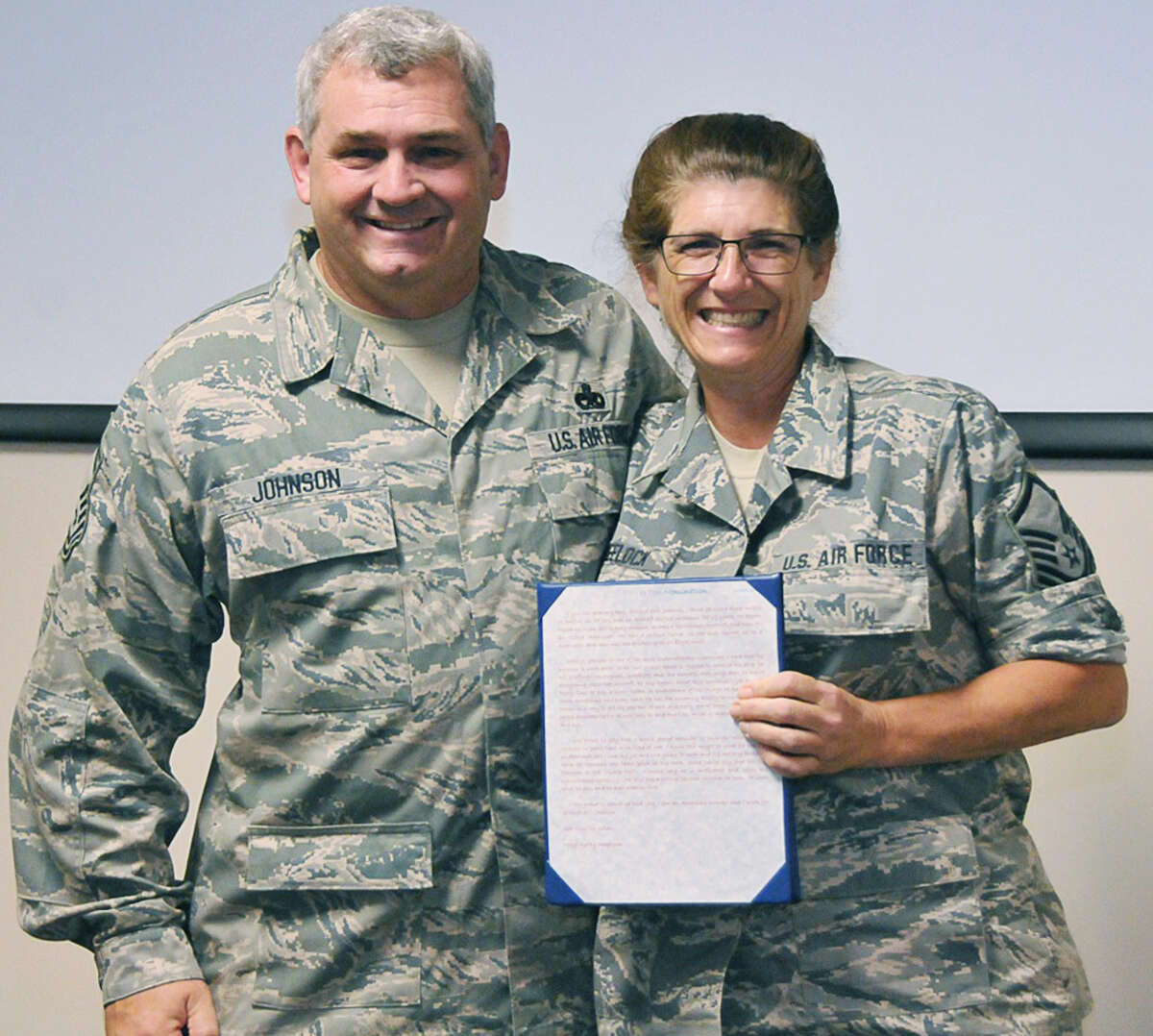 Senior Master Sergeant Eric Johnson, a New Milford native, gladly poses for a keepsake photo with Master Sergeant Kathy Wheelock, who holds a tribute letter she wrote about her United States Air Force boss. Johnson is expected to retire in 2017 after 38 years in service to his country. April 2015