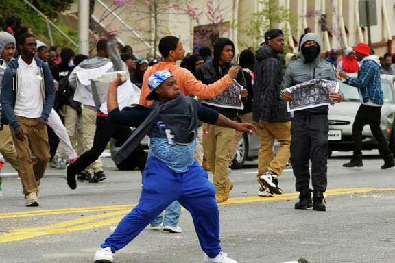 Demonstrators throw rocks at the police, after the funeral of Freddie Gray, on Monday, April 27, 2015, at New Shiloh Baptist Church in Baltimore. Gray died from spinal injuries about a week after he was arrested and transported in a Baltimore Police Department van. (AP Photo/Jose Luis Magana)