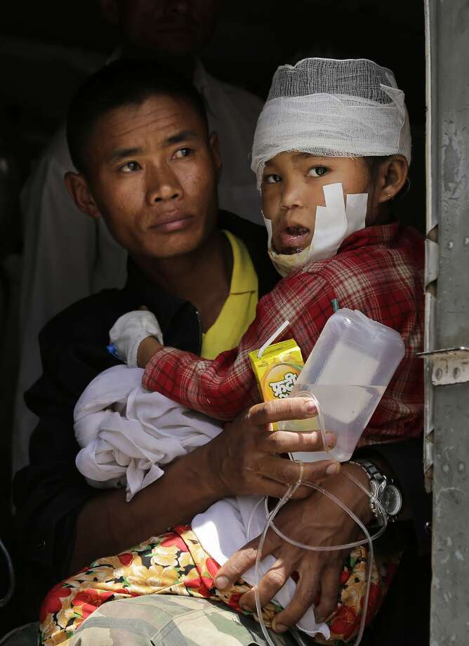 A child injured in Saturday's earthquake, is carried by a Nepalese soldier after being evacuated as they wait to disembark from an Indian Air Force helicopter at the airport in Kathmandu, Nepal, Monday, April 27, 2015. The death toll from Nepal's earthquake is expected to rise depended largely on the condition of vulnerable mountain villages that rescue workers were still struggling to reach two days after the disaster. (AP Photo/Altaf Qadri) Photo: Altaf Qadri, Associated Press