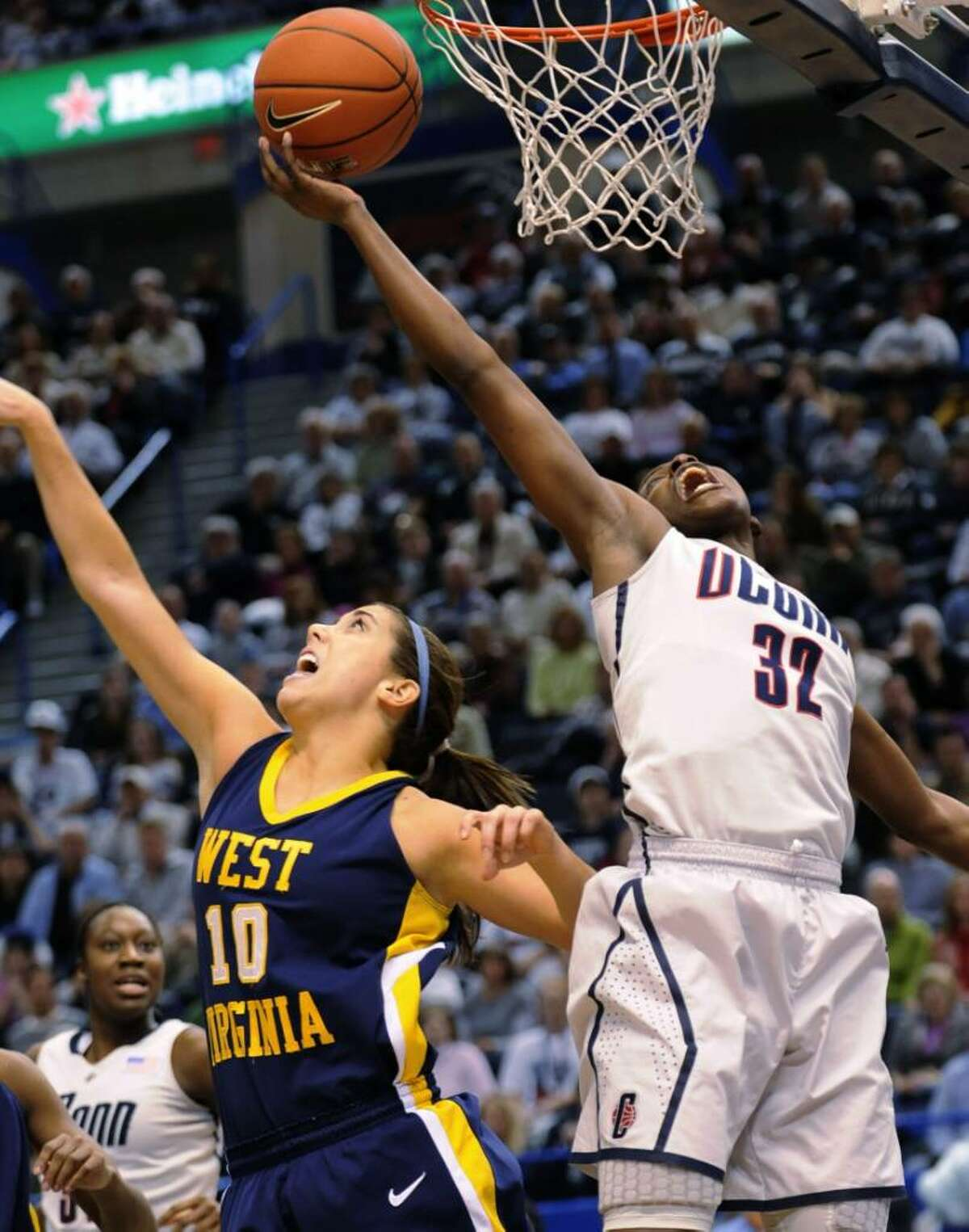 Connecticut's Kalana Greene shoots next to West Virginia's Liz Repella during the first half of an NCAA college basketball game for the championship of the Big East women's tournament in Hartford, Conn., Tuesday, March 9, 2010. (AP Photo/Bob Child)