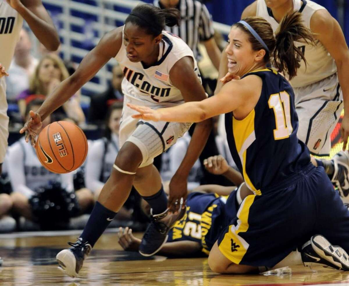 Connecticut's Kalana Greene pulls in a loose ball as West Virginia's Liz Repella also tries for it during the first half of an NCAA college basketball game for the championship of the Big East women's tournament in Hartford, Conn., Tuesday, March 9, 2010. (AP Photo/Bob Child)