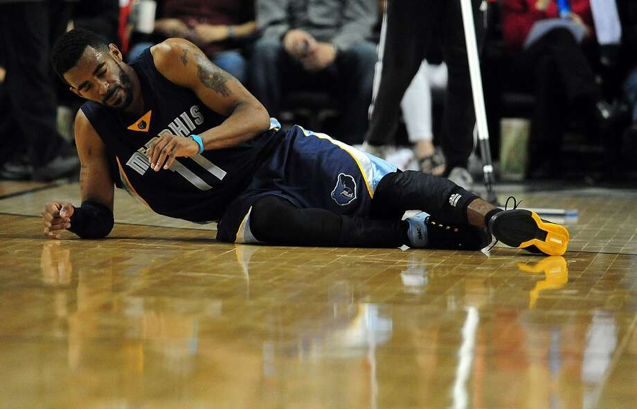 Mike Conley  of the Memphis Grizzlies rolls over on the court after being hurt during the third quarter in Game 3 of the Western Conference quarterfinals against the Portland Trail Blazers. Photo: Steve Dykes, Getty Images