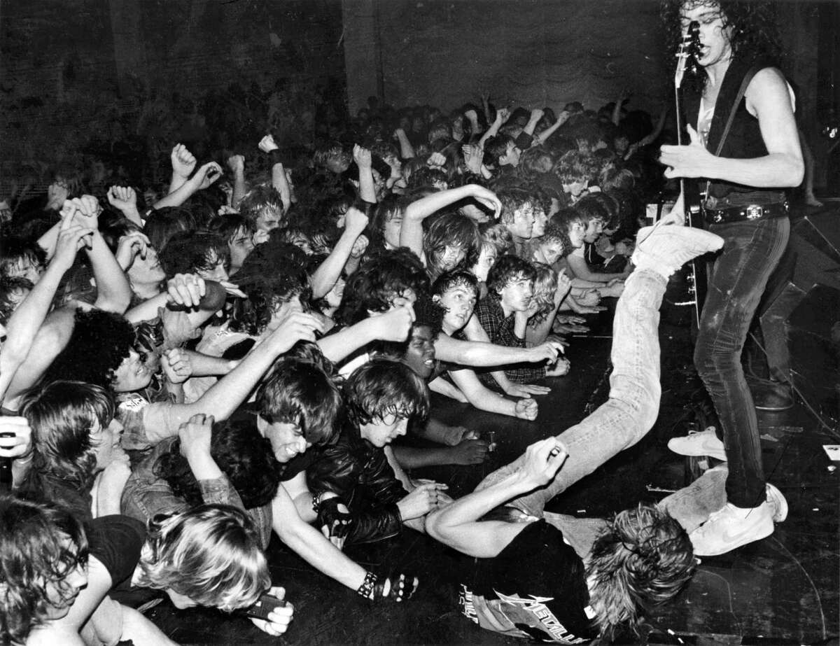 March 15, 1985: A young heavy-metal fan rolls at the feet of Metallica guitarist Kirk Hammett at the Kabuki Theater after being lifted out of the crowd and passed overhead.
