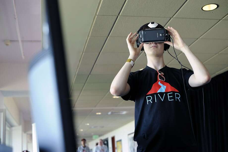 A guest tries out VR goggles at the Solirax booth during a demo day event hosted by virtual reality-specific accelerator River at AT&T Park in San Francisco. Photo: Michael Short, Special To The Chronicle