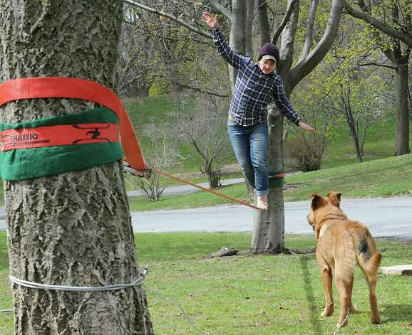 Staphanie Levine of Albany practices her slacklining skills as her dog Charley watches in Washington Park on Monday, April 27, 2015 in Albany, N.Y.  (Lori Van Buren / Times Union) Photo: Lori Van Buren