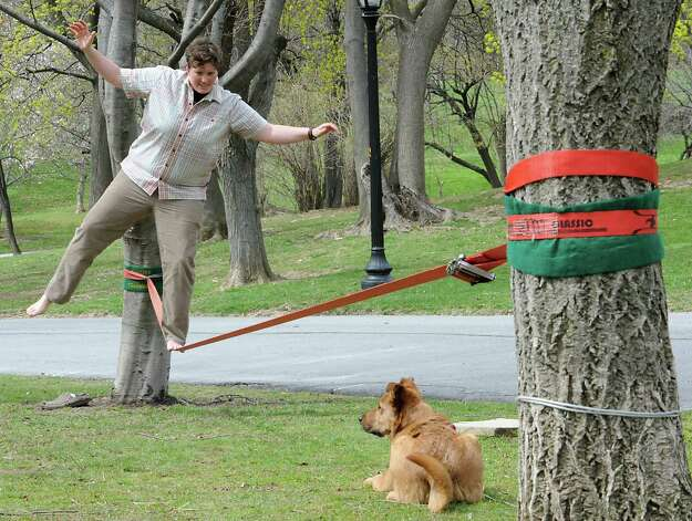 Kelsey Lane of Albany works on her slacklining skills as her friend's dog Charley watches in Washington Park on Monday, April 27, 2015 in Albany, N.Y.  (Lori Van Buren / Times Union) Photo: Lori Van Buren