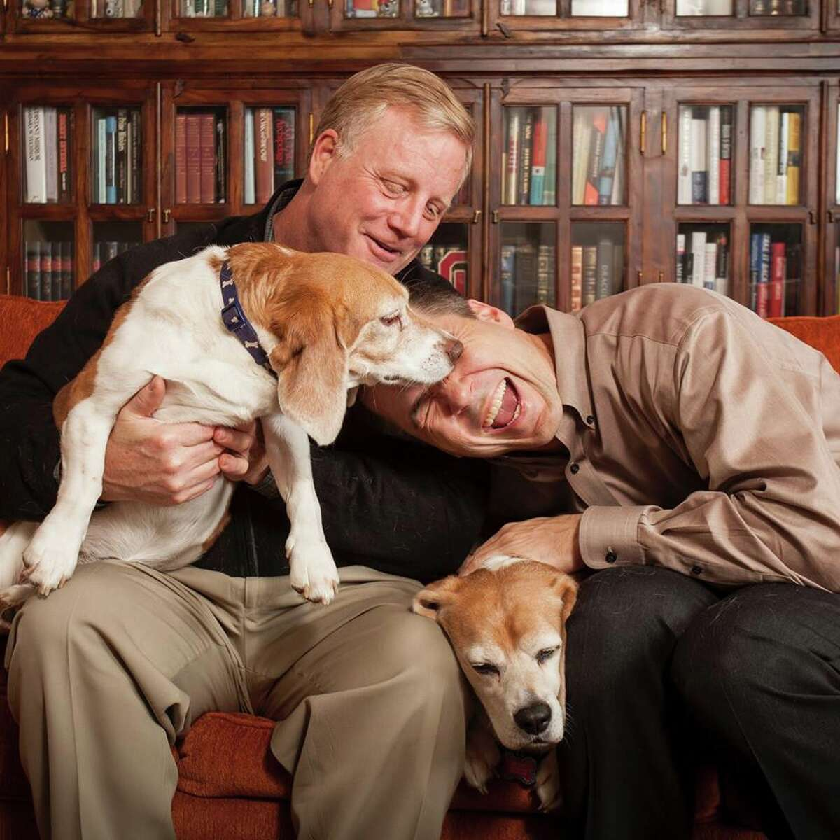 Mark Phariss and Victor Holmes, two of the four plaintiffs in the case challenging Texas' gay marriage ban, play with their dogs in their Texas home.