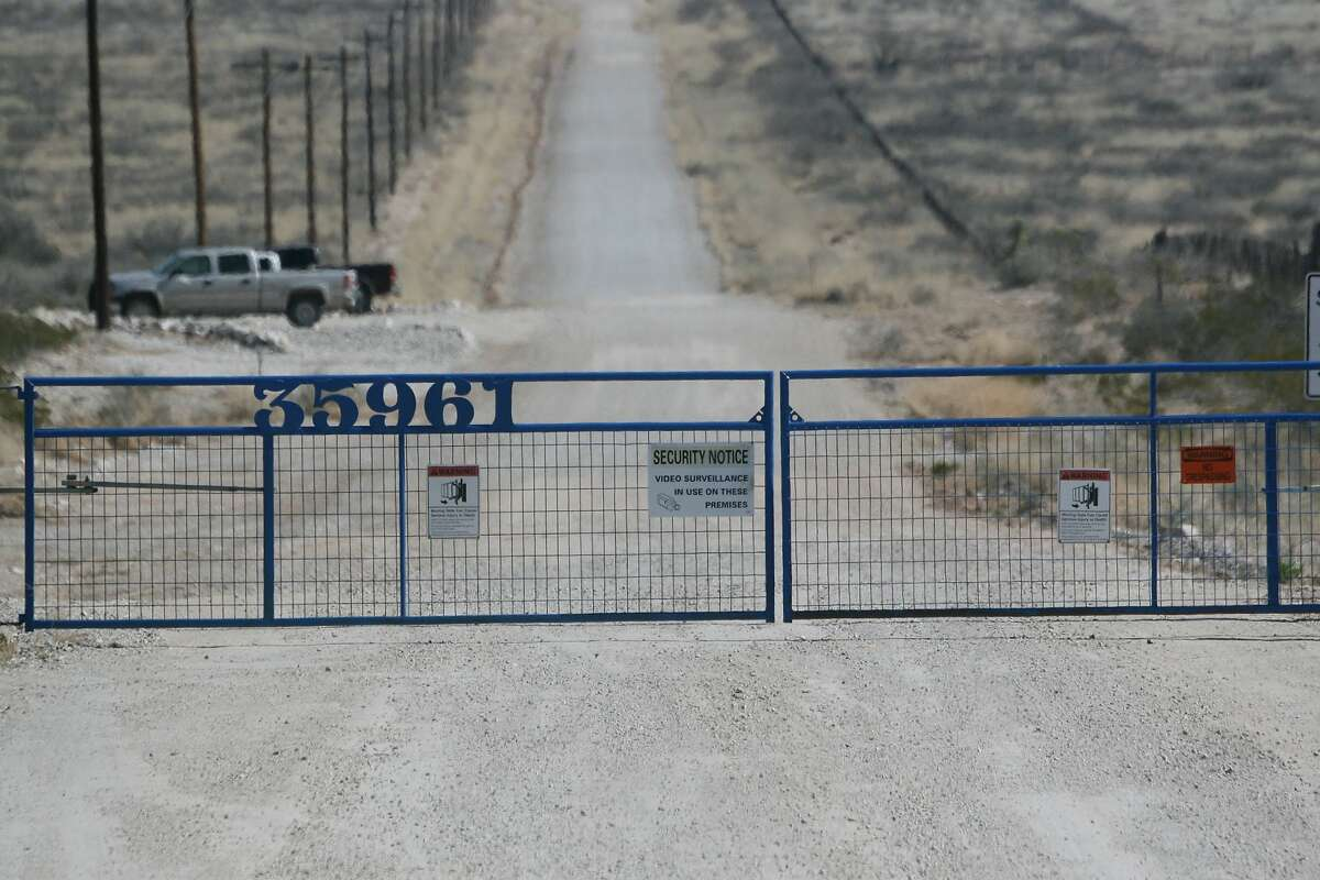 An entrance with a remote-controlled gate miles away from Amazon.com's Jeff Bezos, Blue Origin, can be seen, in Culberson County near Van Horn, Texas on Feb. 17, 2015. In Texas, two internet billionaires whose strategies and personalities seem worlds apart are playing host to a 21st-century space race. Low-key Bezos' Blue Origin is in West Texas. Elon Musk, who helped start PayPal, heads high-profile SpaceX company 600 miles to the southeast. (AP Photo/Mike Graczyk)