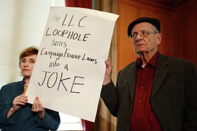 Carol Bullard, left, of Menands and Raymond Lawrence of Albany, both with the advocacy group New York for Democracy, attend a press conference where the Senate Democratic Conference urged their Republican counterparts to pass legislation closing the so called, LLC loophole, Monday morning, April 27, 2015, at the Capitol in Albany, N.Y. limited liability companies (LLCs) are currently allowed to contribute large sums of money to candidates for state office. If passed, senate bill S.60 would close that loophole. (Will Waldron/Times Union) Photo: WW / 00031611A