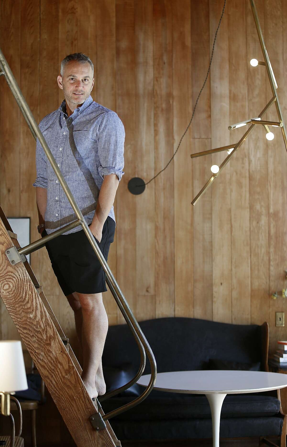 Designer Charles de Lisle shows his home as he uses the stairway from the second floor in Mill Valley, California, on Monday, April 27, 2015. At right is a prototype of a Linden chandelier hanging from the ceiling.