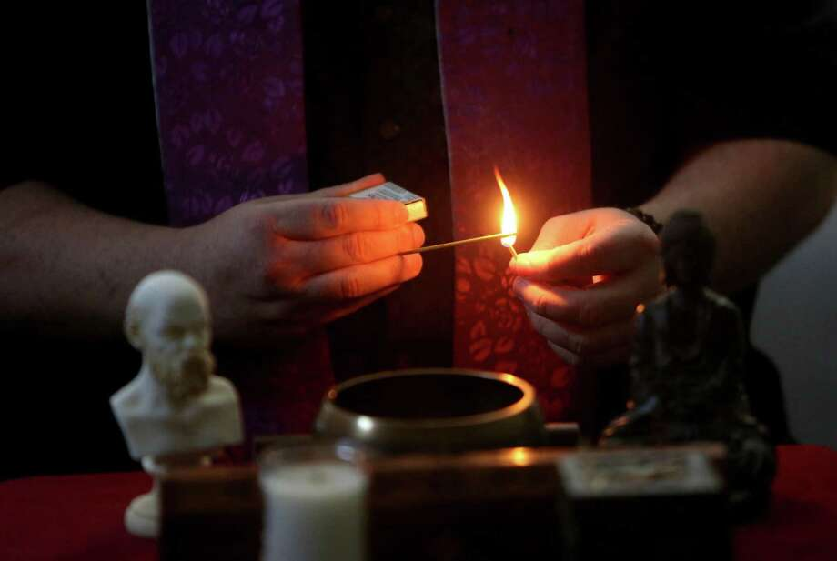 Daniel Strain, founder of the Spiritual Naturalist Society, lights incense Saturday before a service at the Bayland Community Center. He began holding regular group meetings after his wife asked him to practice his teachings and not just preach them. Photo: Gary Coronado, Staff / © 2015 Houston Chronicle