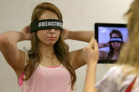 University of Houston junior Jacquelyn Gomez, left, puts on a blindfold for a photo taken by UH senior Michi McMahon in a social media campaign for Austin Tice.