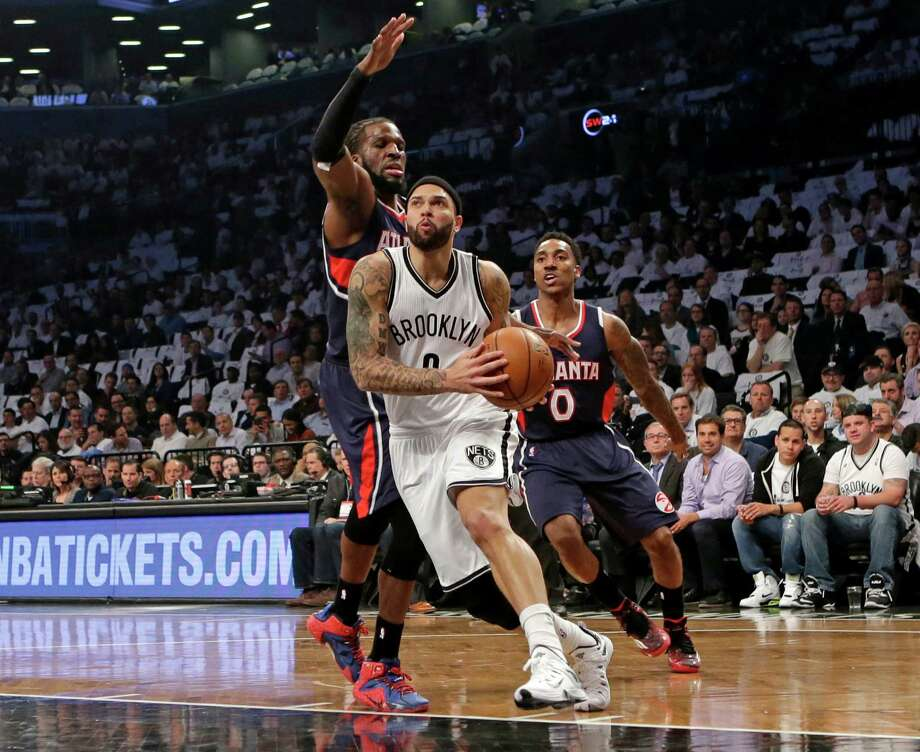 Brooklyn Nets guard Deron Williams (8) drives around Atlanta Hawks forward DeMarre Carroll (5) in the first quarter of Game 4 of a first round NBA playoff basketball game, Monday, April 27, 2015, in New York. (AP Photo/Kathy Willens) ORG XMIT: NYKW208 Photo: Kathy Willens / AP