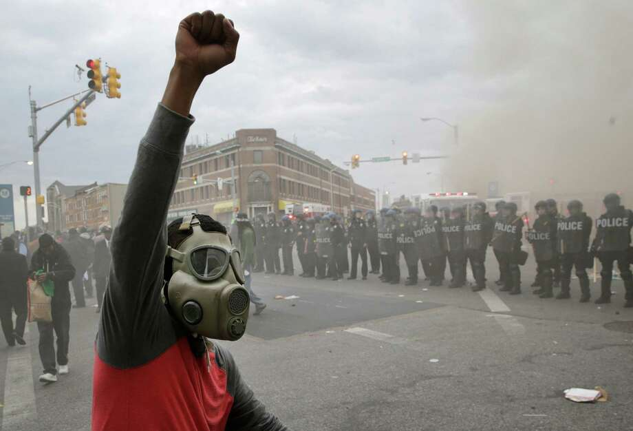 A demonstrator stands in front of a police line as a store burns Monday in Baltimore. Photo: Patrick Semansky, STF / AP