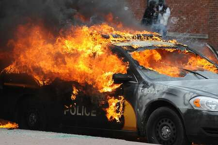 An officer vehicle burns Monday, April 27, 2015, during unrest following the funeral of Freddie Gray in Baltimore. Rioters plunged part of Baltimore, torching a pharmacy, setting police cars ablaze and throwing bricks at officers. (Jerry Jackson/The Baltimore Sun via AP)