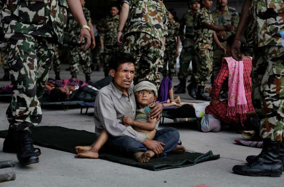 A man sits with a child on his lap as victims of Saturday's earthquake, wait for ambulances after being evacuated at the airport in Kathmandu, Nepal, Monday, April 27, 2015. The death toll from Nepal's earthquake is expected to rise depended largely on the condition of vulnerable mountain villages that rescue workers were still struggling to reach two days after the disaster.  (AP Photo/Altaf Qadri) ORG XMIT: DEL197 Photo: Altaf Qadri / AP
