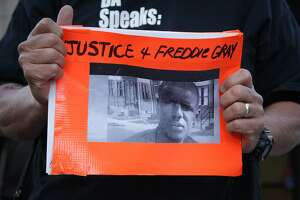 On Monday April 27, 2015 in Oakland, California, activists gather in Oakland outside the Federal building in solidarity with people in Baltimore who are protesting the police killing of Freddie Gray. An activist holds an image of Freddie Gray.