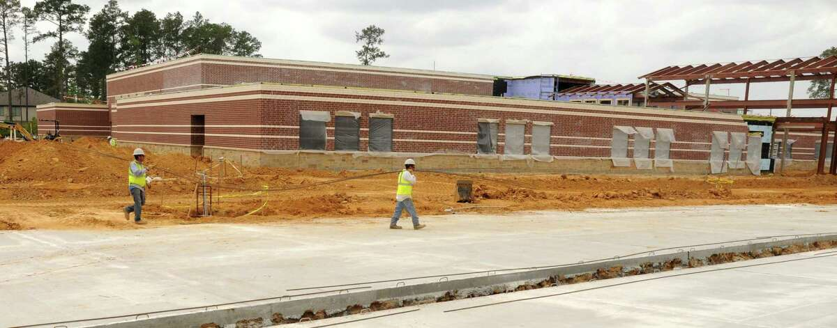 Workers carry rebar past the front of the Creekview Elementary School, 8877 West New Harmony Trail in The Woodlands. The Tomball ISD school will open in the fall. Photograph by David Hopper