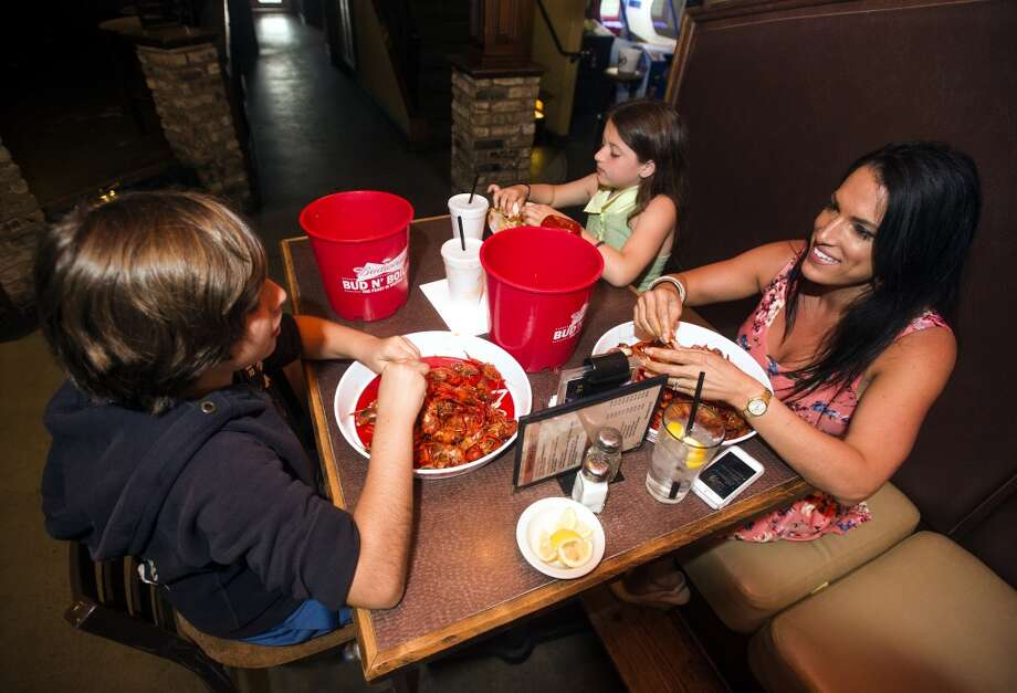 Zane Seelke, 11, left, eats crawfish with Patrice Seelke, right front, and Tawni Seelke, 7, at Madison's on Tuesday evening. Madison's serves up crawfish several times throughout the week during the season. Photo taken Tuesday 3/31/15 Jake Daniels/The Enterprise Photo: Jake Daniels/The Enterprise