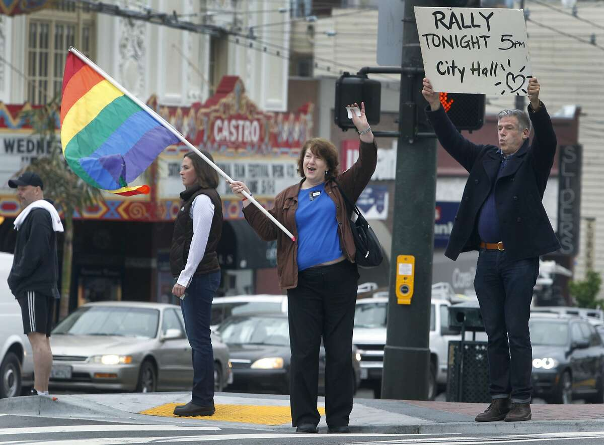Joanie Juster (left) and Gregg Cassin urge commuters driving past Market and Castro streets to attend an afternoon rally at City Hall in San Francisco, Calif. on Tuesday, April 28, 2015 to support same sex marriage. The U.S. Supreme Court was hearing oral arguments on the marriage equality issue while the group gathered at Harvey Milk Plaza in the morning.