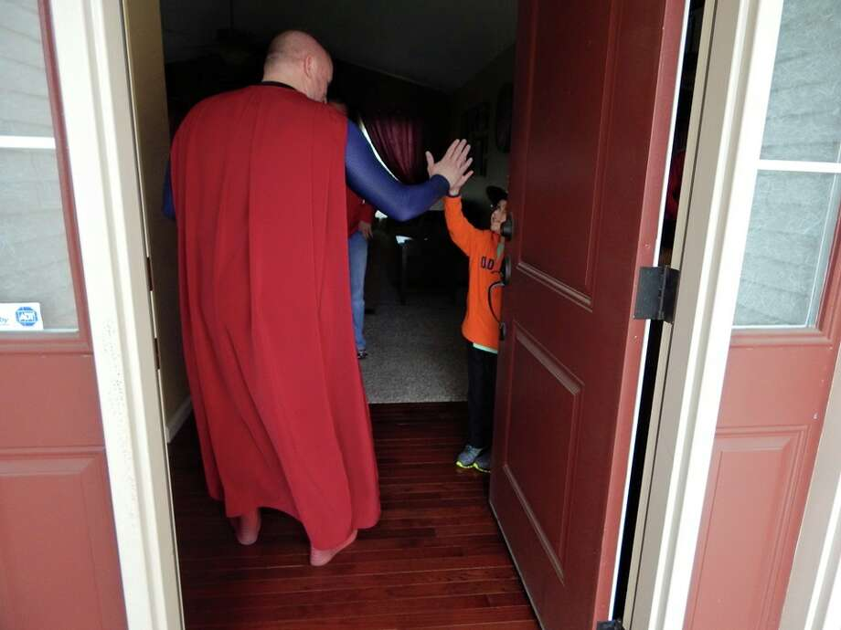 Brian Schottel, 7, answers his front door to find Superman, portrayed by Senior Cpl. Damon Cole of the Dallas Police Department, April 14, 2015. Photo: Courtesy Of Senior Cpl. Damon Cole