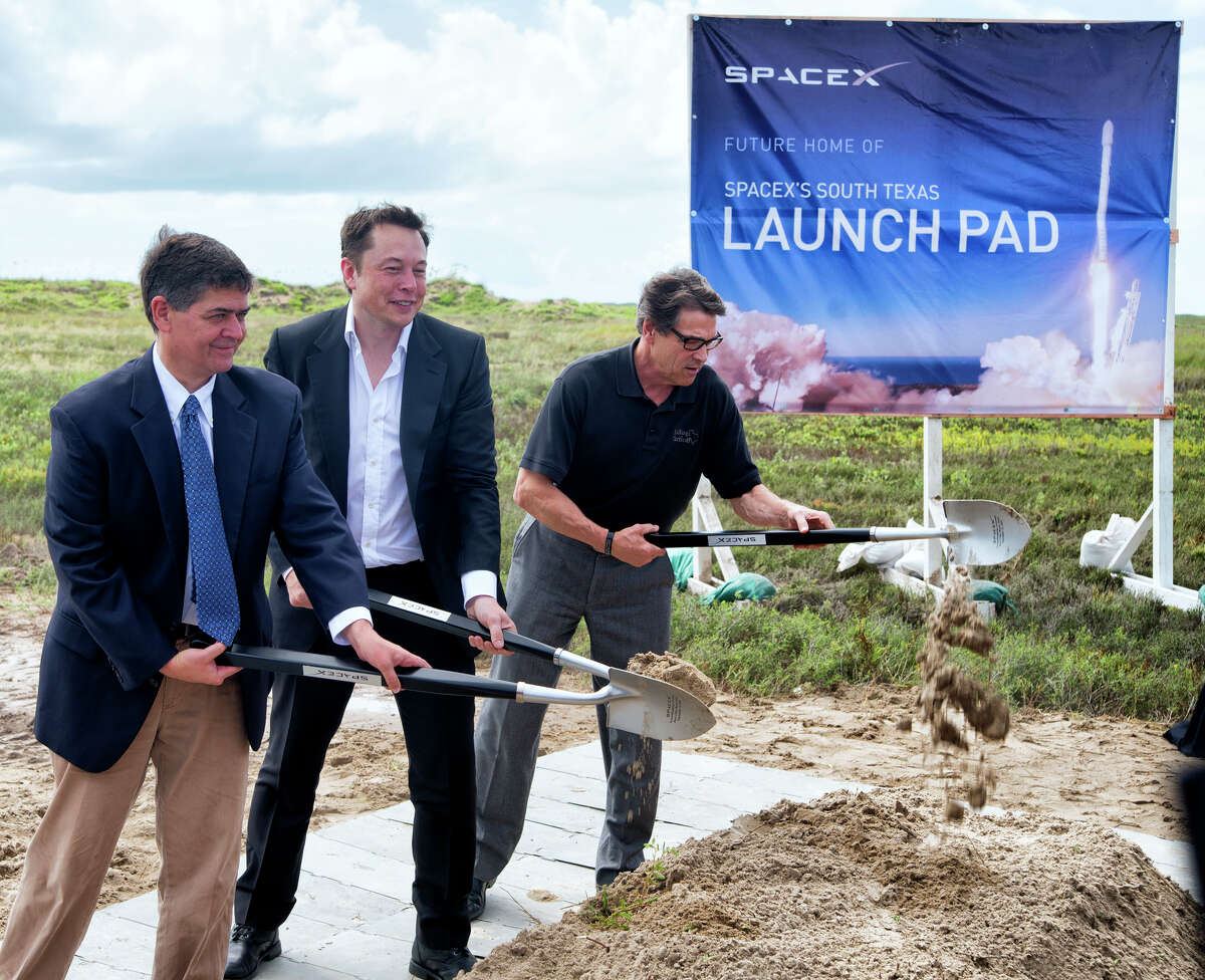 In a Sept. 22, 2014 file photo, U.S. Rep. Filemon Vela, left, SpaceX founder and CEO Elon Musk, center, and Texas Gov. Rick Perry turn the first shovel-full of sand at the groundbreaking ceremony for the SpaceX launch pad at Boca Chica Beach, Texas. The SpaceX venture, led by PayPal co-founder and electric car maker Musk, is one of two parts of the 21st-century space race being directed in the Texas by Internet billionaires.