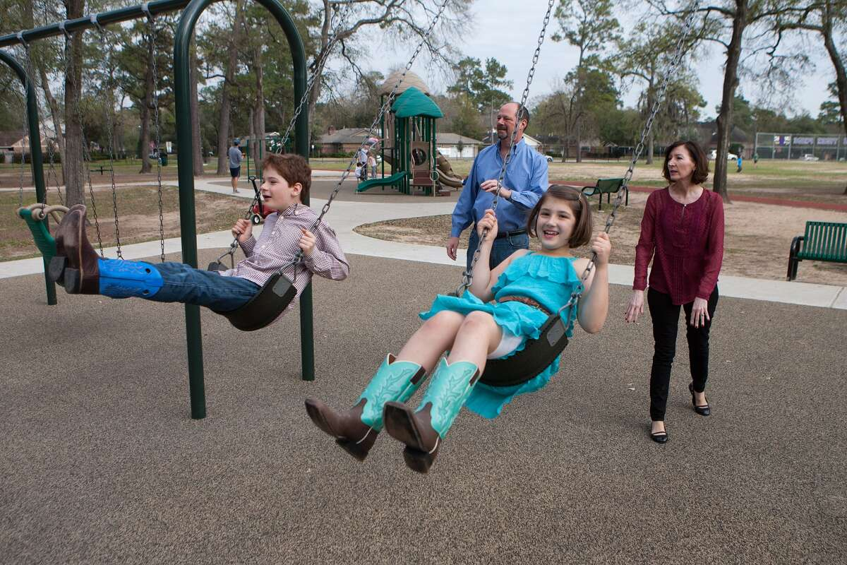 Peter and Carol Gilmore and their 9 year old twins, Deveny and Clayton,at play in the Spark Park at Frostwood Elementary School, which has become something of a gathering point for the neighborhood. Photo By R. Clayton McKee