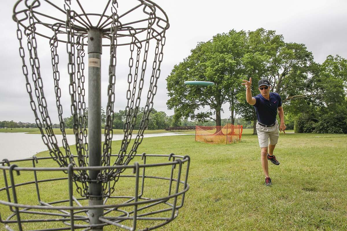 """Bridgeland resident and disc golfer Ramsey Womack """"putts"""" at the Bridgeland disc golf course in Cypress. Womack enjoys living in the master-planned community, citing the atmosphere and the variety of activities available to residents."""