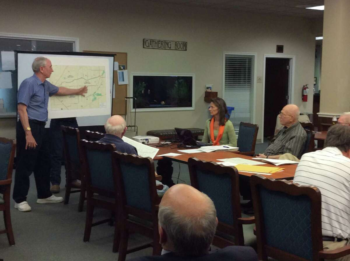 At a recent Brays Bayou Association meeting, Bruce Krewinghaus, left, identifies potential trails that could link neighborhoods to Brays Bayou Greenway. Listeners include Houston Parks Board Executive Director Roksan Okan-Vick, center, and association president Bob Schwartz, right.